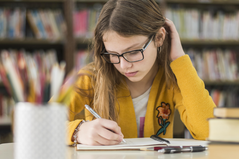 Niña estudiando en una biblioteca